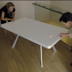 A corian table embedded with 2400 LED lights and 2 trackpads turns it into a modern version of the 1972 Atari Pong game. Designed by Moritz Waldemeyer, it's part of MoMA's  Design & the Elastic Mind Exhibit.