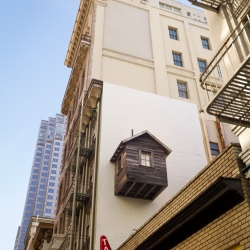 Mark Reigelman's new work, Manifest Destiny!, shows a cabin attached to one of the remaining spaces not being used in cities – over and between other buildings.