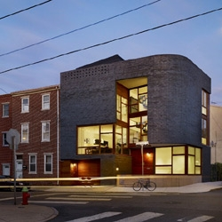 By Qb, this newly constructed split-level house stitches itself into the Philadelphia neighborhood. Curved brick corners negotiate the irregular street grid, while a palette of brick volumes and stone bases are translated into a new vocabulary.