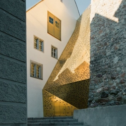 What looks like an angular stack of gilded dominoes is actually the bronze façade of the Rapperswil-Jona Municipal Museum designed by the architects at :mlzd.