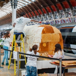 A huge train cake was constructed at London's Paddington Station to celebrate 15th birthday of the Heathrow Express.