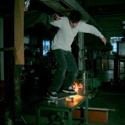 Seattle-based glassblower Robert G. Burch attempts to skateboard across molten glass.