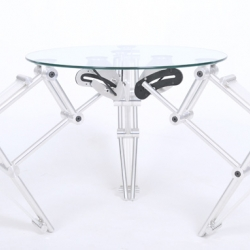 The Push Up Table is made from aluminum, glass and silicon tube and works just like a clicky pen. Push down on the table and it raises up. Push down again and it lowers.
