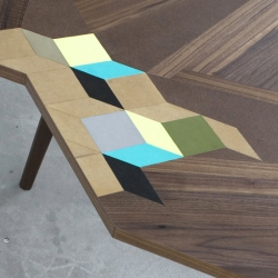 TABLES OF CONTENTS by American designer Paul Isabella is a table designed with complex geometric marquetry and a unique juxtaposition of materials.
