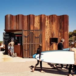 A wavy little coffee shop has washed up on the shores of Torquay, using recycled sheet piles that were used in the 2010 floods as temporary formwork for sandbanking overflowing rivers.