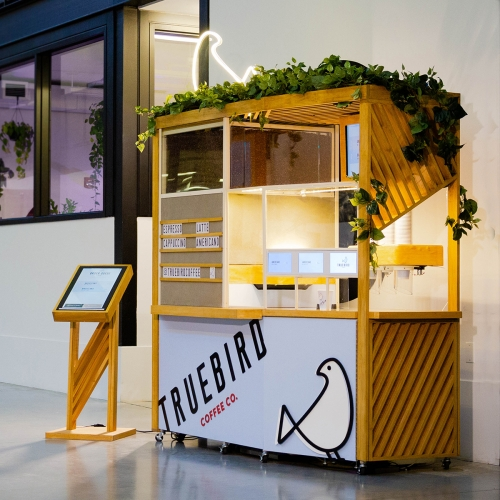 Automated Micro-Cafe designed by Leadoff Studio for Truebird Coffee. The kiosk brews, pours, and serves cups of coffee, which can be ordered from the Truebird app or ordering stand.