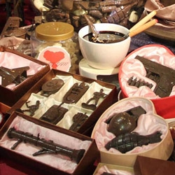 Tu Wei-Cheng's atypical chocolate shop. A large-scale installation that alongside its pink walls and hearts contains chocolate hand grenades, soldiers, guns and other miniature chocolate arms and artillery.