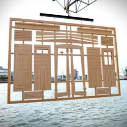 Form Scratch, a life size wooden toy house building kit by French duo artists Kolkoz hangs over the Rhine during Art Basel 2014.