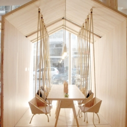 The kid friendly Fiii Fun House by Íris Cantante in Buenos Aires, Argentina featuring a variety of spaces including a table with swings for chairs.
