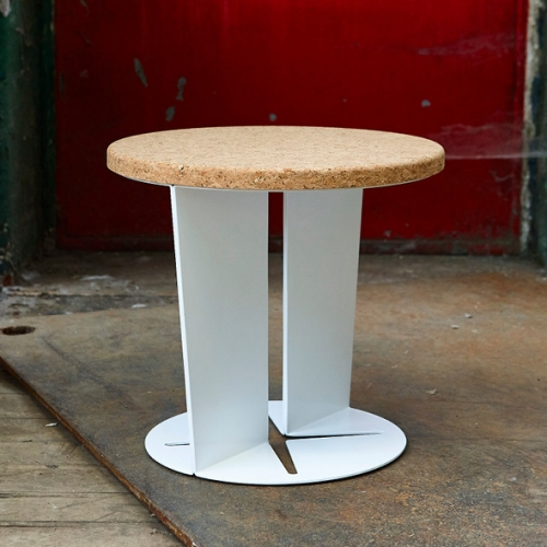 Pedestal by Lee Walsh plays with convention - the profile of an archetypal pedestal table has been removed to create a three-dimensional negative. Powder coated steel with cork top.