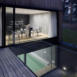 Seaside House, a home from Ultra Architects in Poland with a timber clad exterior and concrete interior walls.