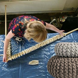 Giant knitting needles are used to hand made these giant  Flocks Poufs.