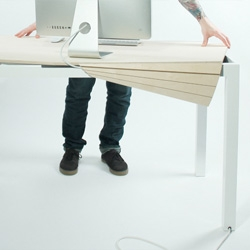Michael Bambino's Tambour Table, a personal computer table whose tabletop can be gently pushed away to reveal power, usb connections, and compartments that allow the user to store items or quickly clear the table surface.