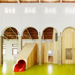 Miquel Mariné Núñez and César Rueda Boné's Centro Infantil del Mercado, a school created in a former market hall. Love the integrated slide!