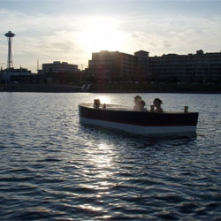 Hot tub boats navigating the waters of Lake Union. This summer, lounge in a luxurious soaking tub, with sweeping views of the Seattle skyline.