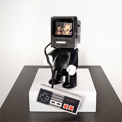 German designer Hannes Hummel turned this vinyl Qee figure into a retro gaming machine using the guts from a Game Boy Advance and an old NES controller.