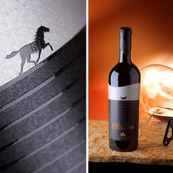 The Stallion Wine of Angelus Estate's label depicts a running horse with gloss puff-up varnish contrasting with a black matte finish. The logo of Angelus Estate is printed with matte copper hotfoil symbolizing the mountains, sky and soil.