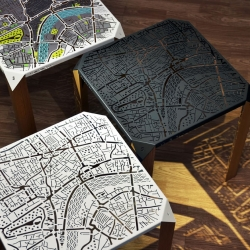London Map Side Table - A concept from Hasan Agar. The London street map and landmarks are engraved on a metal surface. It has matte beech triangular section legs and comes in three different options: black, white and watercolours.