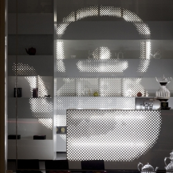 This T shop in Copenhagen is designed as if the whole store were the display. Tiny backlit holes perforate the shelves on surfaces at different depths, creating a powerful eye-catcher from outside.