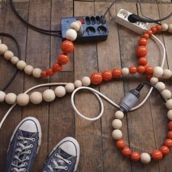 Nathalie Costes is known for her wooden bead necklaces, but she also turns ugly extension lead into beautiful electric chains covered by dyed wooden beads
