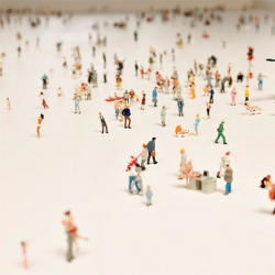 511 miniature figures representing all walks of life, genders and ages walk alone in a crowd just beneath the surface of a table by Rolf Sachs called Alone in a Crowd.