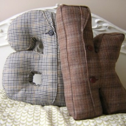 These pillows are made from recycled suit-jackets. Some will have buttons, some will have a pocket, all retro awesome tweeds, herringbones and checks ...