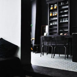 Sleep in the City is a trio of apartments available as short-term rentals in the fashion district of Antwerp, an ideal base from which to explore the city. Stylish interiors feature vintage furniture painted matte black against a backdrop of white.