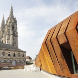 A new archeological museum, clad in a rusted metal skin, is situated next to a 12th-century Gothic cathedral in Soissons, France.