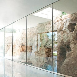 Barud House in Jerusalem by Paritzki & Liani architects uses glass to show off the beautiful bare cliff walls.