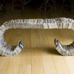 """As a part of  the """"X days project"""",  the """"334"""" bench is made of three parallel bars of metal and 334 old newspapers folded and stacked next to each other."""