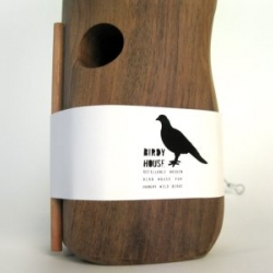 Azul's simple packaging to wrap pieces together. The walnut bird perch separate from the seed container,wrapped with a simple belt of paper. The food packaging has a  bird shaped window.