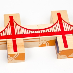 Bridge Blocks, six screen printed puzzles that tell the story of building bridges. Each side depicts a different step in the bridge building process, from steel molecules to smelting steel to cranes with girders.