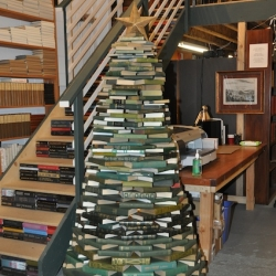 We had a holiday party last weekend at the warehouse and perhaps the centerpiece of the event (and certainly the item that attracted the most attention) was our 7 foot tall Christmas tree made entirely of green books!