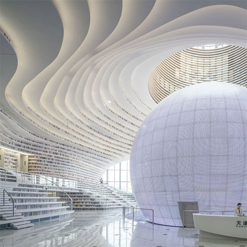 Tianjin Binhai Library in China designed by MVRDV. With a capacity of 1.2 million books, the 34,000 square meter space features an otherworldly spherical structure in the centre and mesmerizing undulating bookshelves.