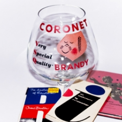 "In the early 1940s, Paul Rand designed a new logo for CORONET. The illustrative ""waiter"" made its way into numerous advertising materials and posters through the mid-1950s, including a nine-inch tall giant brandy snifter glass. Paul Rand would've turned 96 this year..."