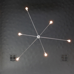 A light weight tensegrity structure makes the bulbs of Brendan Ravenhill's Cord chandelier appear to float.