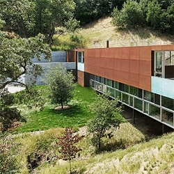 Stanley Saitowitz's Bridge House sits gently over the california landscape, spanning over a small creek. The rusted steel panels make the house age and blend with the surroundings.