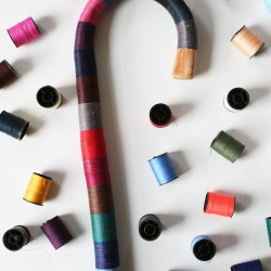 Dominic Wilcox's Multi-coloured thread is hand wound onto a walking stick. Each stick is unique and takes about fifteen hours to make. On sale at YCN, London