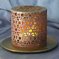 This is an old hairspray canister that has been meticulously worked into a filigree pattern candle holder.