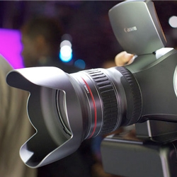 Canon shows off their 4K resolution technology with a multi-purpose video and photo camera. The camera has a center mounted lens with a grip on the right, large viewfinder and pop-up digital display.
