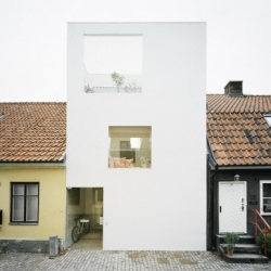Between a line of traditional houses, a perfect pristine white box designed by Elding Oscarson appears, breaking the monotony of the street.
