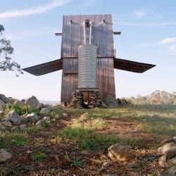 Permanent Camping is a 10x10x20ft 'tower' in the Australian bush, clad in corrugated copper (protection from the elements), with 3 folding sides (for shade and security), a sleeping loft,  kitchen, outhouse and rainwater tank. Very cool.