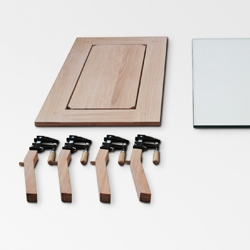 """nonlinear's RTA coffee table has four wood clamps as principal fasteners; 40"""" x 22"""" x 17"""", the table packs flat at 40"""" x 22"""" x 3"""". Made from pickled oak and steel clamps with a 1/2"""" tempered glass top."""