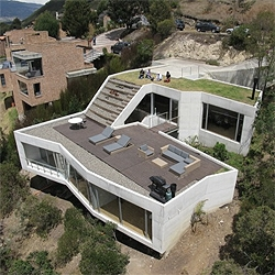 Colombian architects Plan B + Giancarlo Mazzanti recently completed this interesting house on a hill. The structure desegregates to be part of the slope, resulting in a deck with an amazing view over the local wetlands.