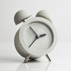 HOBBY:DESIGN creates a desktop clock using nothing but cement. The clock is minimalist in appearance, but decorative with its two bell-like fixtures on top.