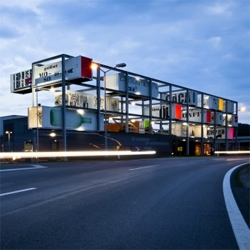 'Genussregal' is a landmark, an exhibition hall, a shop within the logistics, storage place, designed as a large scale wine rack, using containers. By BWM Architekten & Partner.