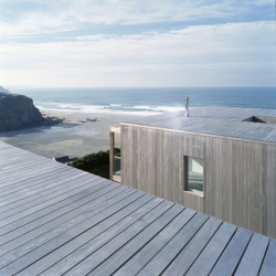 British firm Simon Conder Associates built two wooden houses into the side of a steep hill in the English coastal village of Porthtowan.