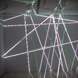 Video of 'Dial M for Murder' installation by Daniel Canogar. A video animation is precisely aimed at  a VHS tape lattice of lines spreading across an exhibition space.