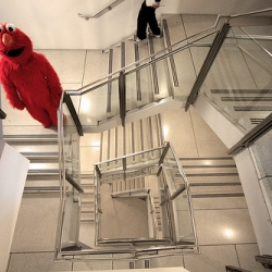 Elmo meets M.C. Escher.  Set of bizarre photos of life-sized Elmo doing the town by Mark Sebastian.