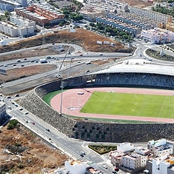 A giant stadium in Tenerife, Spain. It is enclosed by a giant stone wall that makes it look like a crater. By AMP Arquitectos.